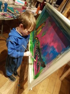 Child working on landscape painting with a bird on a branch using pointillism as a painting technique.